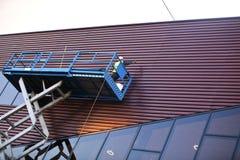 Construtor em uma plataforma do elevador do Scissor imagem de stock