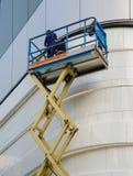 Construtor em uma plataforma do elevador do Scissor Imagens de Stock