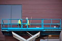 Construtor em uma plataforma do elevador do Scissor em um canteiro de obras Fotografia de Stock Royalty Free