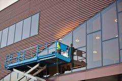 Construtor em uma plataforma do elevador do Scissor em um canteiro de obras Foto de Stock