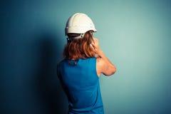 Construtor fêmea novo no telefone imagem de stock royalty free