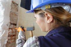 Construtor fêmea que usa o martelo e o formão imagens de stock