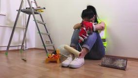 Construtor fatigante da mulher que senta-se no assoalho perto da escada de etapa video estoque