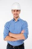 Construtor feliz do homem no capacete de segurança que está com os braços cruzados foto de stock