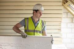 Construtor Fitting Insulation Boards no telhado da casa nova Fotografia de Stock Royalty Free