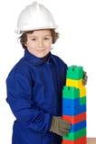 Construtor futuro adorável que constrói uma parede de tijolo com parte do brinquedo Fotos de Stock Royalty Free