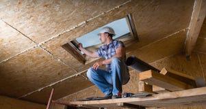Construtor Inspecting Skylight na casa inacabado imagem de stock