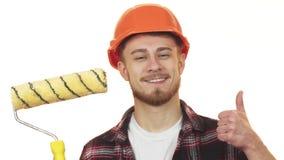 Construtor masculino novo feliz que guarda o rolo de pintura que mostra os polegares acima vídeos de arquivo