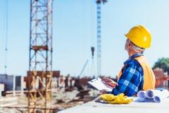 construtor na veste reflexiva e no capacete de segurança que estão no canteiro de obras com prancheta foto de stock