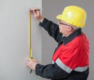 Construtor no capacete de segurança amarelo que determina a distância Fotos de Stock
