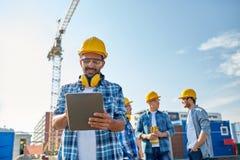 Construtor no capacete de segurança com o PC da tabuleta na construção Foto de Stock Royalty Free