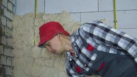 Construtor no desgaste do trabalho que põe o emplastro sobre a parede ventilada do bloco de cimento video estoque
