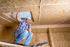 Construtor no telefone celular dentro da casa inacabado fotos de stock