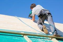 Construtor no trabalho com construção de madeira do telhado fotos de stock