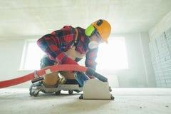 Construtor no trabalho cortando o assoalho concreto para cabografar pela máquina de corte do diamante imagens de stock