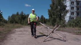 Construtor no Walkietalkie perto da construção da proteção com arame farpado video estoque