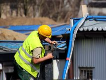 Construtor nos macacões no canteiro de obras Reparos na altura Construção de edifícios novos A profissão de um construtor Hea fotografia de stock