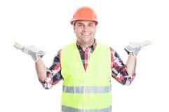 Construtor novo alegre que guarda algo em suas palmas Fotografia de Stock