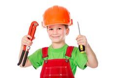Construtor pequeno no capacete com chave e chave de fenda Foto de Stock