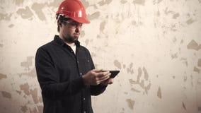 Construtor profissional em um capacete e vidros em uma sala video estoque