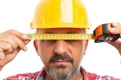 Construtor que cobre os olhos com a fita de medição fotos de stock royalty free