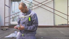 Construtor que conta seu salário que está no canteiro de obras vídeos de arquivo