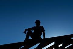 Construtor que descansa sobre a estrutura de telhado Fotografia de Stock
