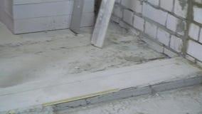Construtor que faz medidas com fita e o lápis de medição no canteiro de obras