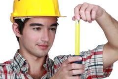 Construtor que guarda a fita métrica Foto de Stock Royalty Free