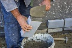 Construtor que guarda um tijolo e com a pá de pedreiro da alvenaria que espalha e sh Fotografia de Stock