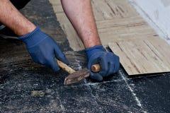 Construtor que levanta telhas de assoalho velhas em uma passagem Imagens de Stock Royalty Free