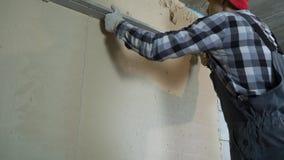 Construtor que nivela o emplastro na parede ventilada do bloco de cimento com régua da construção video estoque