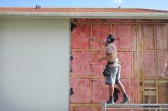 Construtor que remove uma isolação velha da parede da fibra de vidro de um buildi imagem de stock royalty free
