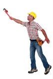 Construtor que tenta alcançar algo. fotografia de stock royalty free
