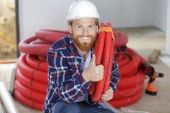 Construtor que transporta as tubulações ao mostrar o polegar acima fotos de stock royalty free