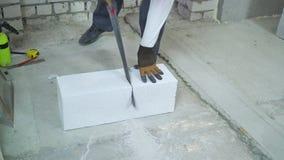 Construtor que vê o bloco de cimento ventilado ao longo da linha tirada com serra de mão video estoque