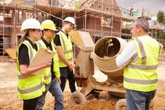 Construtor Using Cement Mixer no terreno de construção com aprendizes fotografia de stock