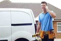 Construtor With Van Talking On Mobile Phone fora da casa imagens de stock