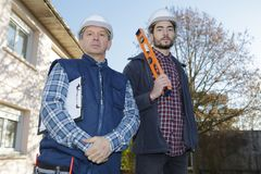 Construtores levando do homem novo ao nível no canteiro de obras foto de stock royalty free