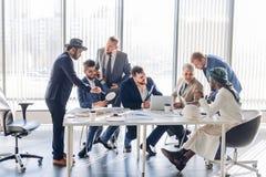 Construtores masculinos sérios dos colegas que verificam o funcionamento do esboço na equipe para cooperar imagens de stock