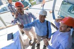 Construtores no canteiro de obras com o contratante que revê o projeto de Buiding, homem de Team Meeting With Architect Business imagens de stock