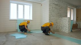 Construtores que isolam o assoalho em uma grande casa fotografia de stock royalty free