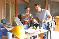 Construtores que relaxam durante a ruptura no local imagens de stock