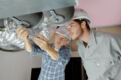 Construtores que trabalham nas tubulações da ventilação fotos de stock
