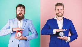 Construya su autodisciplina Los trajes formales del negocio de los hombres sostienen los despertadores Falta de gesti?n de la aut fotografía de archivo