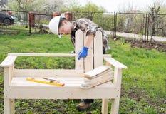 Construyendo un banco del jardín al aire libre Muchacho en casco con un screwdriv Imagen de archivo
