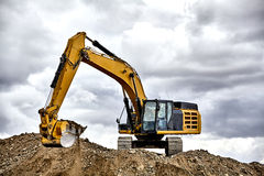 Constuction industry excavator heavy equipment moving gravel fil Stock Photography