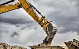Constuction industry heavy equipment excavator dumping gravel Royalty Free Stock Photography