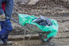 Constuction worker with bricks in wheelbarrow stock images