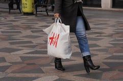 CONSUERS MIT SCHWEDISCHER EINKAUFSTASCHE DER KETTEN-H&M Lizenzfreie Stockfotos